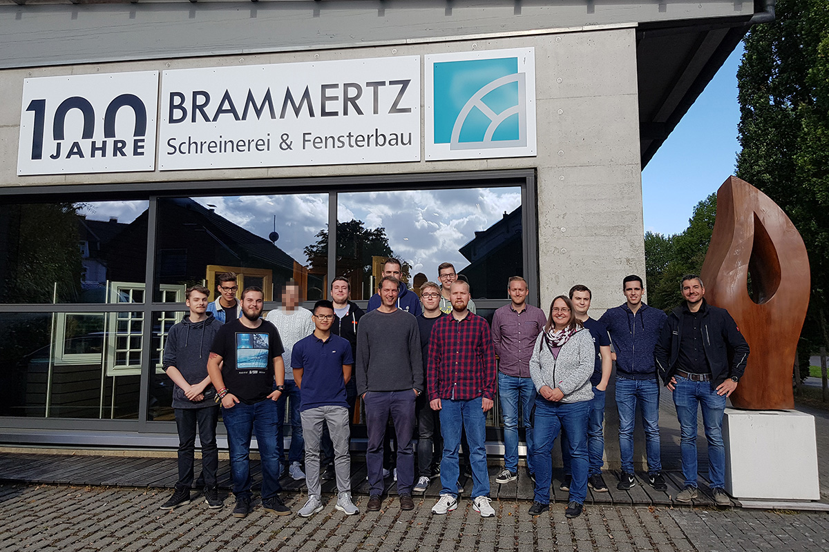 "The managing director Max Brammertz (1st from right) with the Klaes team next to the company logo ""AKKURATESSE""."